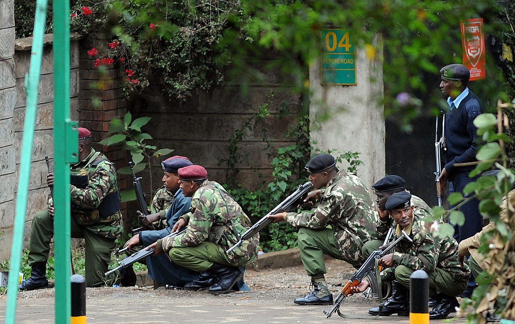 Description of . Armed Kenyan policemen take cover outside the Westgate mall in Nairobi on September 23, 2013. AFP PHOTO / SIMON MAINA/AFP/Getty Images