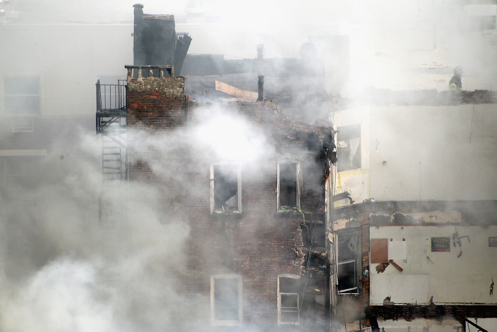 Description of . A firefighter from the Fire Department of New York (FDNY) walks on a roof  during a five-alarm fire and building collapse at 1646 Park Ave in the Harlem neighborhood of Manhattan March 12, 2014 in New York City.   (Photo by Justin Heiman/Getty Images)