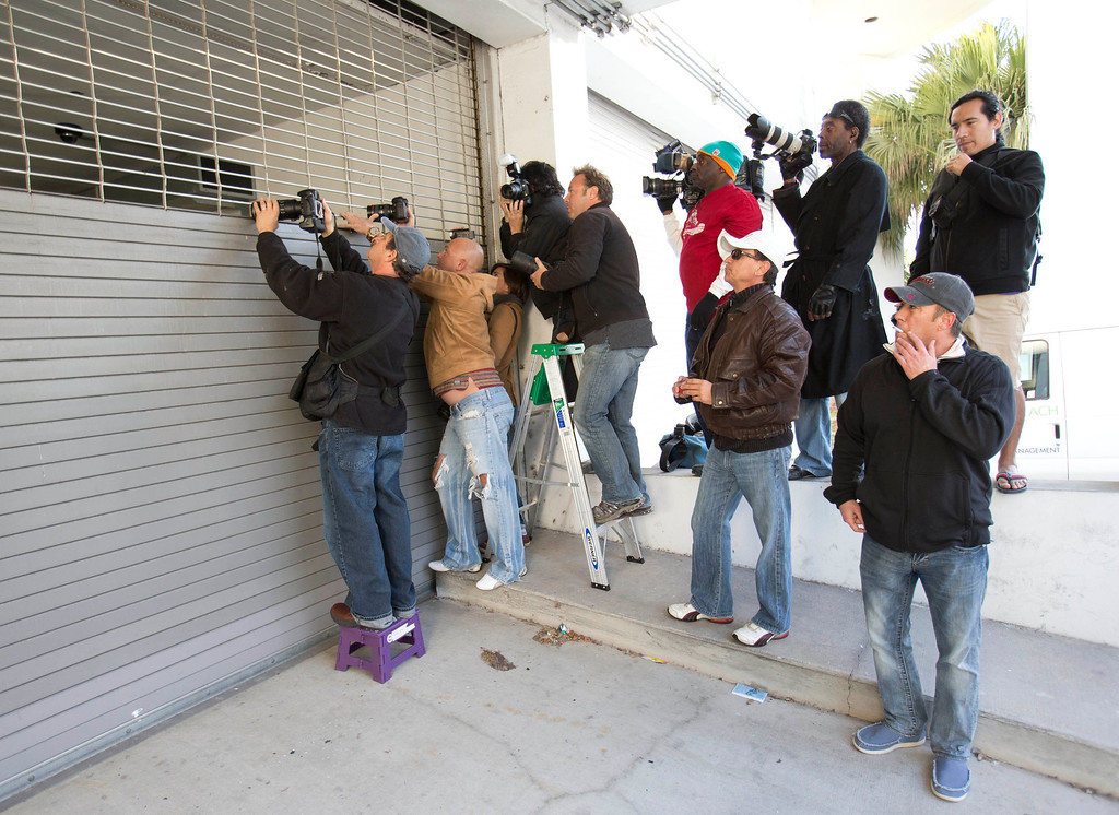 . Photographers jockey for position as they wait for police to transport pop singer Justin Bieber, Thursday, Jan. 23, 2014 in Miami Beach, Fla. Police have Bieber and R&B singer known as Khalil for alleged drag-racing on a Miami Beach street. (AP Photo/Wilfredo Lee)