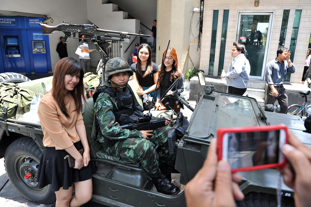 . Passersby pose for a photo with Thai army soldiers standing guard on a city centre street after martial law was declared on May 20, 2014 in Bangkok, Thailand. The army imposed martial law across Thailand amid a deepening political crisis that has seen six months of protests and claimed at least 28 lives. (Photo by Rufus Cox/Getty Images)