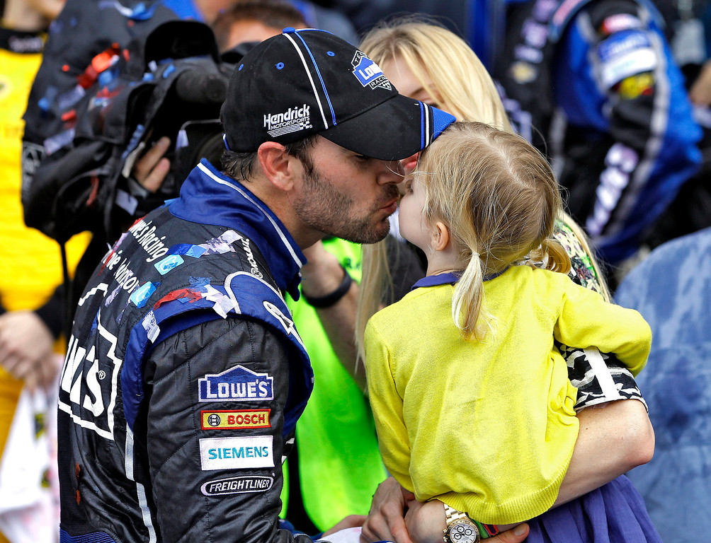 Description of . Jimmie Johnson kisses his daughter Genevieve Marie in Victory Lane after winning the Daytona 500 NASCAR Sprint Cup Series auto race, Sunday, Feb. 24, 2013, at Daytona International Speedway in Daytona Beach, Fla. (AP Photo/Terry Renna)