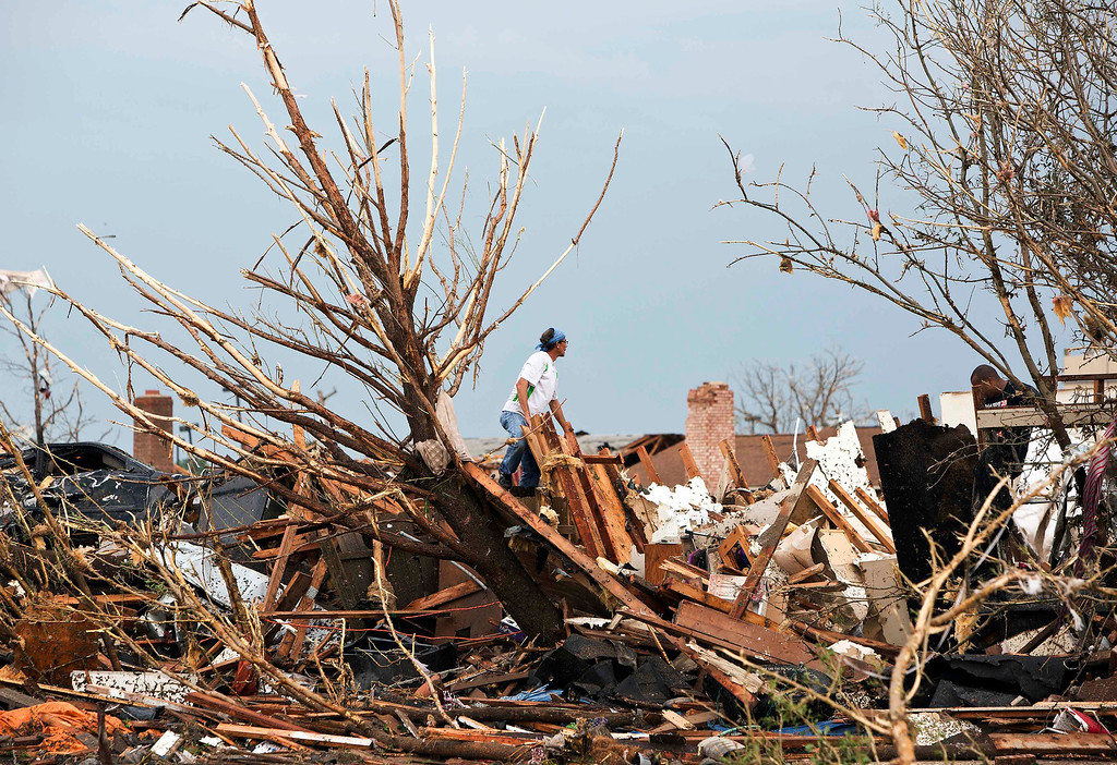 . A man looks through the remains of a home after a huge tornado struck Moore, Oklahoma, near Oklahoma City, May 20, 2013. A massive tornado tore through the Oklahoma City suburb of Moore on Monday, killing at least 51 people as winds of up to 200 miles per hour (320 kph) flattened entire tracts of homes, two schools and a hospital, leaving a wake of tangled wreckage.    REUTERS/Richard Rowe