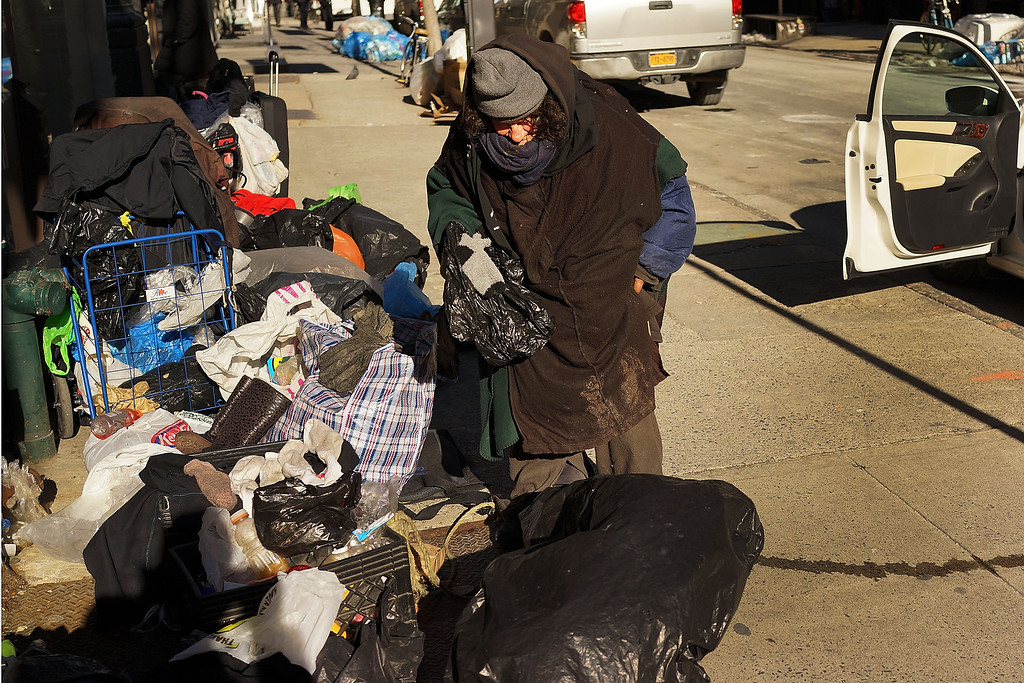 Description of . A homeless woman is layered in clothes as she sorts her possessions during subzero cold weather on January 7, 2014 in New York City. A
