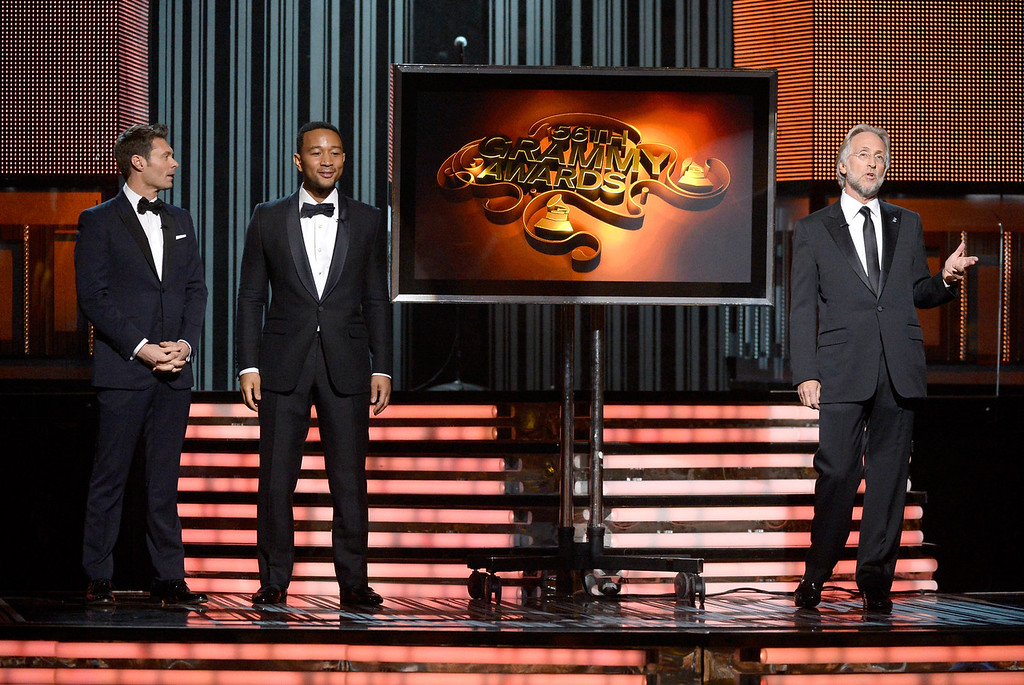 Description of . (L-R) TV personality Ryan Seacrest, musician John Legend, and Recording Academy President Neil Portnow speak onstage during the 56th GRAMMY Awards at Staples Center on January 26, 2014 in Los Angeles, California.  (Photo by Kevork Djansezian/Getty Images)