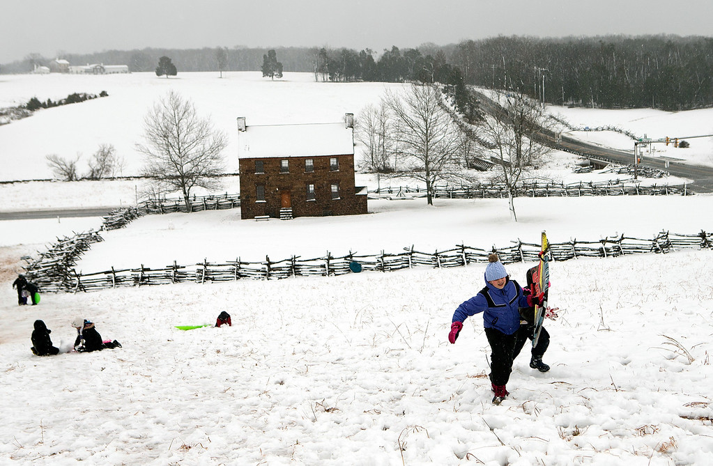 Description of . Annie Castro (L) and Sophia Benedetto battle gusting winds and snow to reach the top of a sledding hill on the grounds of Manassas Battlefield Park March 6, 2013 in Manassas, Virginia. A winter storm hit the Washington, DC area today with areas west of the city seeing signficant snowfall, but the city itself seeing minimal snow. (Photo by Win McNamee/Getty Images)