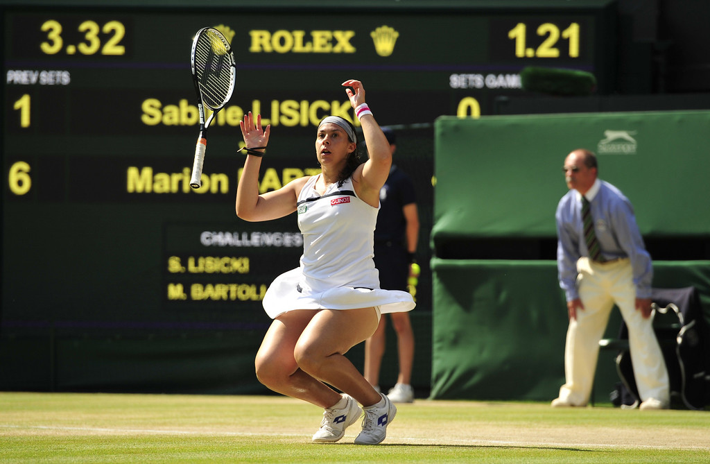 Description of . France's Marion Bartoli drops her racquet and falls to her knees as she beats Germany's Sabine Lisicki in their women's singles final match on day twelve of the 2013 Wimbledon Championships tennis tournament at the All England Club in Wimbledon, southwest London, on July 6, 2013.  GLYN KIRK/AFP/Getty Images