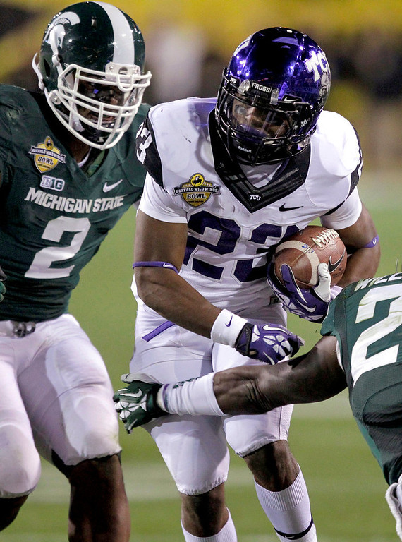 Description of . TCU running back B.J. Catalon (23) gains yards as Michigan State Spartans defensive end William Gholston (2) defends during the first half of the Buffalo Wild Wings Bowl NCAA college football game, Saturday, Dec. 29, 2012, in Tempe, Ariz. (AP Photo/Matt York)