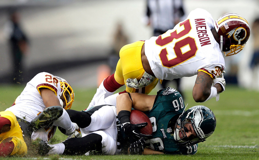 Description of . Philadelphia Eagles tight end Zach Ertz (86) is tackled by Washington Redskins cornerback Josh Wilson, left, and free safety David Amerson (39) during the first half of an NFL football game in Philadelphia, Sunday, Nov. 17, 2013. (AP Photo/Matt Rourke)