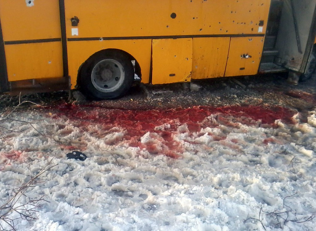 Description of . This handout picture taken and released on January 13, 2015 by Anti-Terrorist Operation (ATO) press service shows snow covered with blood and a damaged bus after it was hit by a long-range Grad rocket apparently fired by pro-Russian insurgents in Volnovakha. Ten Ukrainian civilians were killed and nearly 20 injured in the attack.  Local police said the rocket appeared to have gone astray after being aimed by the gunmen at a checkpoint set up by government soldiers on the main highway connecting the rebel stronghold of Donetsk with Ukraine's southeastern coast on the Sea of Azov. HO/ ANTI-TERRORISTS OPERATION (ATO) PRESS SERVICE /AFP/Getty Images