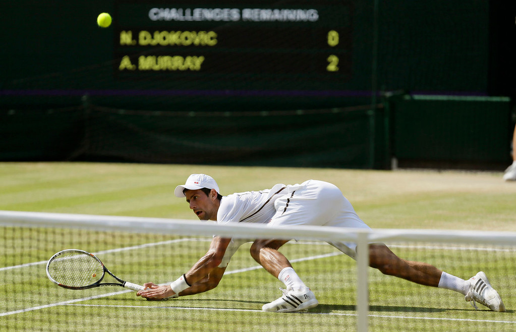 Description of . Novak Djokovic of Serbia plays a return to Andy Murray of Britain during the Men's singles final match at the All England Lawn Tennis Championships in Wimbledon, London, Sunday, July 7, 2013. (AP Photo/Alastair Grant)