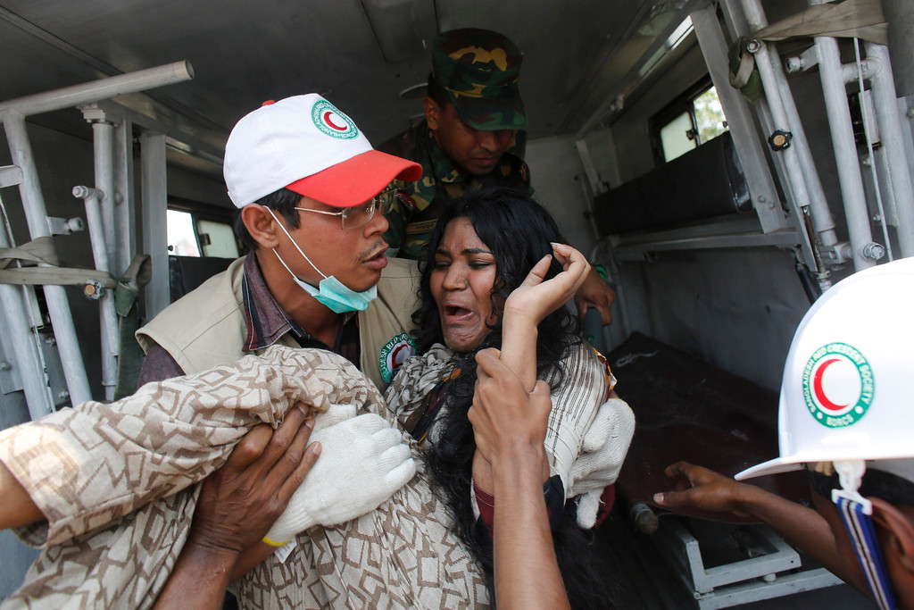 Description of . A rescue worker carries a garment worker to an ambulance after pulling her from the rubble of the collapsed Rana Plaza building in Savar, 30 km (19 miles) outside Dhaka April 24, 2013.  REUTERS/Andrew Biraj