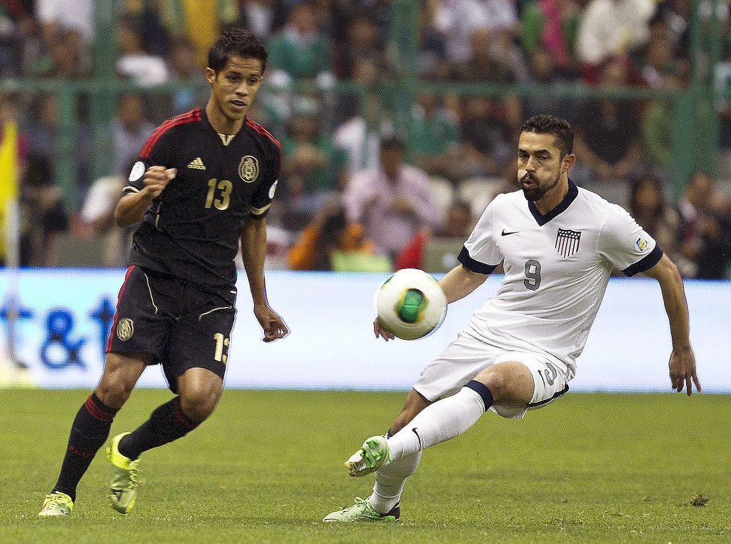 Description of . United States' Herculez Gomez, right, and Mexico's  Severo Meza vie for the ball during a 2014 World Cup qualifying match at the Aztec stadium in Mexico City, Tuesday, March 26, 2013. (AP Photo/Christian Palma)