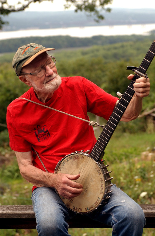 Description of . Pete Seeger, who turned 85 in May 2004, sits on his porch above the Hudson River at Beacon, N.Y. and plays a Woody Guthrie song on his banjo on Tuesday, July 27, 2004.  (AP Photo/Jim McKnight)