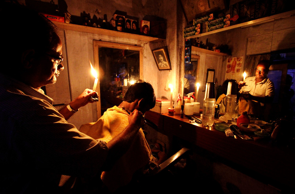 Description of . In this July 31, 2012 file photo, an Indian barber holding a candle,  gives a haircut for a customer at his shop in Kolkata, India. India's energy crisis cascaded over half the country when three of its regional grids collapsed, leaving 620 million people without government-supplied electricity for several hours in, by far, the world's biggest blackout. (AP Photo/Bikas Das, File)