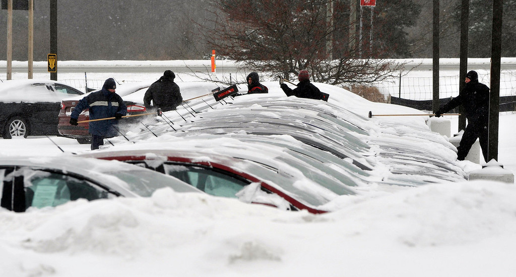 Description of . Employees of a local car dealership clean snow off their front row of new cars in Holly, Mich., Thursday, Jan. 2, 2014.  A multi-day storm dropped up to a foot of snow on parts of Michigan, causing crashes and spinouts on roadways. Snowfall began Tuesday and continued Thursday morning.   (AP Photo/Detroit News,  Charles V. Tines)