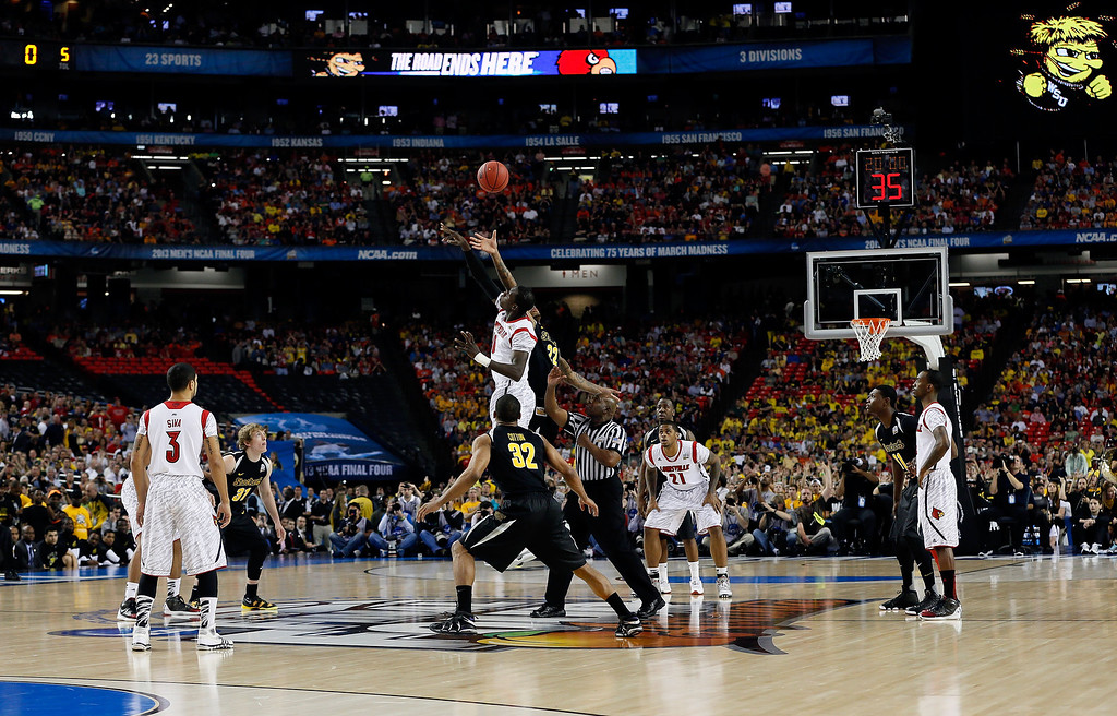 Description of . ATLANTA, GA - APRIL 06:  Carl Hall #22 of the Wichita State Shockers and Gorgui Dieng #10 of the Louisville Cardinals go after the opening jump ball to start the 2013 NCAA Men's Final Four Semifinal at the Georgia Dome on April 6, 2013 in Atlanta, Georgia.  (Photo by Kevin C. Cox/Getty Images)