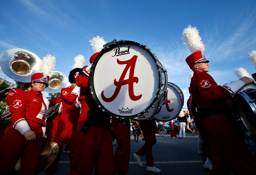 Description of . Alabama Crimson Tide band members walk outside Sun Life stadium before the BCS National Championship college football game between Alabama and the Notre Dame Fighting Irish in Miami, Florida January 7, 2013. REUTERS/Mike Segar