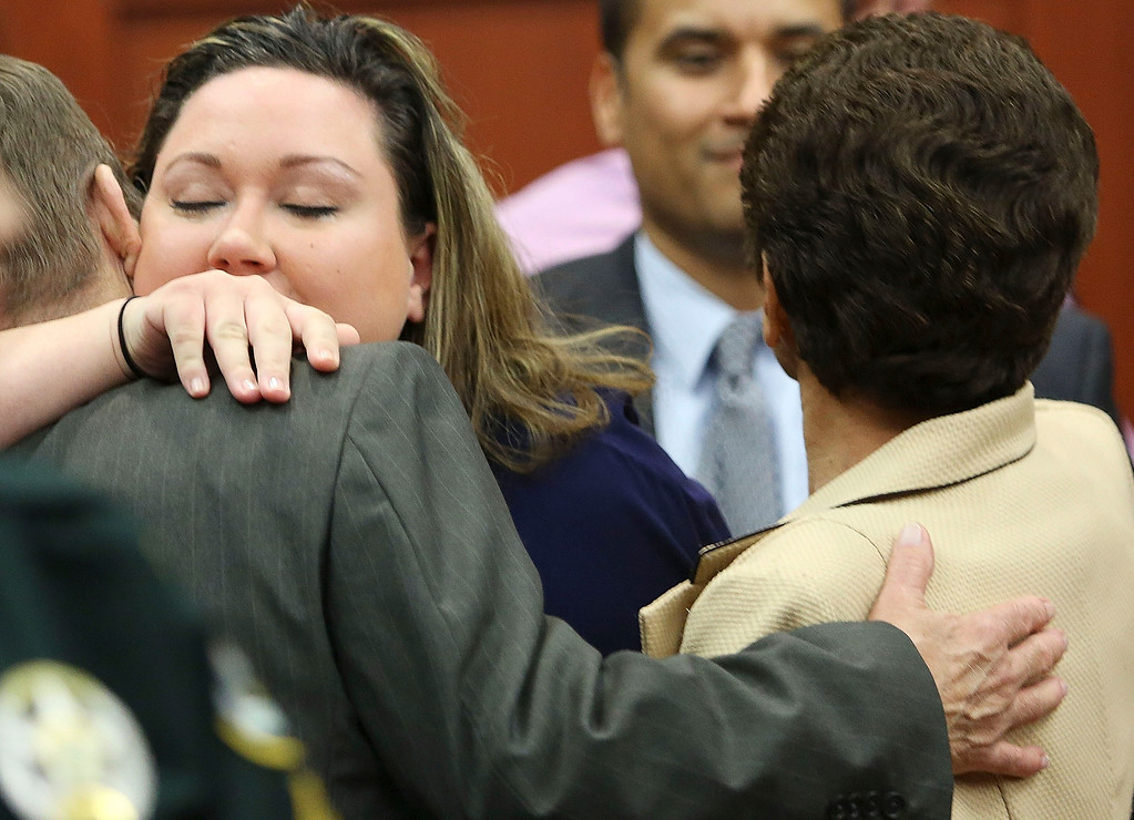 Description of . The wife of George Zimmerman, Shellie Zimmerman, left, hugs Robert Zimmerman Sr. and Gladys Zimmerman after Zimmerman's not guilty verdict was read in Seminole Circuit Court in Sanford, Fla. on Saturday, July 13, 2013. Jurors found Zimmerman not guilty of second-degree murder in the fatal shooting of 17-year-old Trayvon Martin in Sanford, Fla. (AP Photo/Gary W. Green, Pool)
