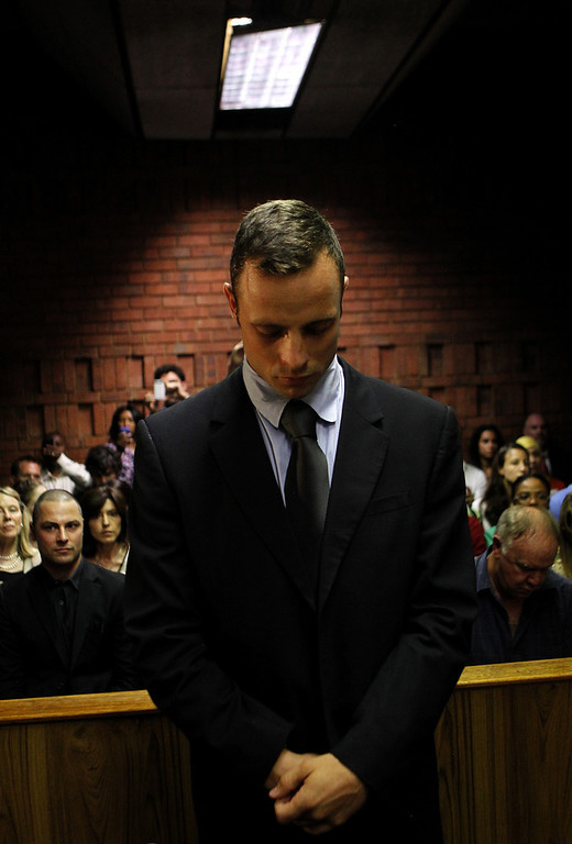 ". Oscar Pistorius stands in the dock ahead of court proceedings at the Pretoria magistrates court February 22, 2013. ""Blade Runner\"" Pistorius, a double amputee who became one of the biggest names in world athletics, was applying for bail after being charged in court with shooting dead his girlfriend, 30-year-old model Reeva Steenkamp, in his Pretoria house.  REUTERS/Siphiwe Sibeko"