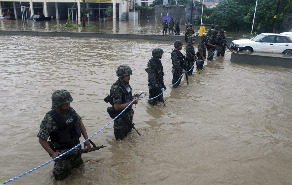 Description of . Mexican Navy members secure a flooded area to prevent theft and robbery in Acapulco, Guerrero state, Mexico, after heavy rains hit the area on September 16, 2013. Hurricane Ingrid weakened to tropical storm strength as it made landfall on the northeastern coast in the morning while the Pacific coast was reeling from the remnants of Tropical Storm Manuel, which dissipated after striking on the eve. Thousands of people were evacuated on both sides of the country as the two storms set off landslides and floods that damaged bridges, roads and homes.   STR/AFP/Getty Images