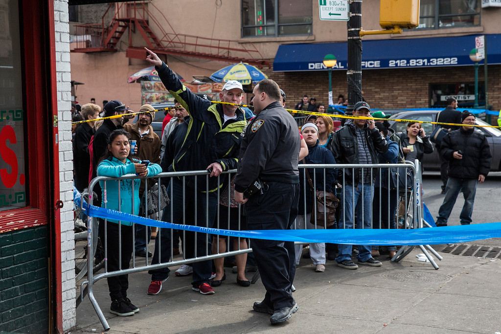 Description of . A crowd watches from behind a barricade as emergency personnel respond to a 5-alarm fire and building collapse at 1646 Park Ave in the Harlem neighborhood of Manhattan March 12, 2014 in New York City.  (Photo by Andrew Burton/Getty Images)