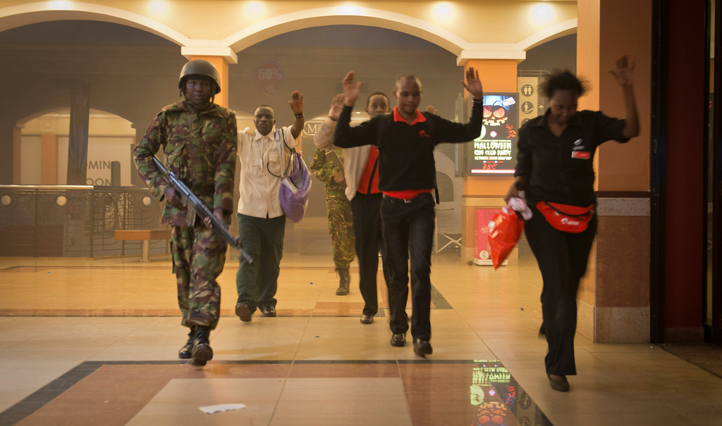 Description of . Civilians who had been hiding during the gun battle hold their hands in the air as a precautionary measure before being searched by armed police leading them to safety, inside the Westgate Mall in Nairobi, Kenya Saturday, Sept. 21, 2013.  (AP Photo/Jonathan Kalan)