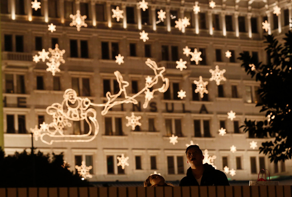 Description of . A couple look at the illuminated decoration to celebrate the festival season during Christmas eve in Hong Kong,Tuesday, Dec. 24, 2013. (AP Photo/Kin Cheung)