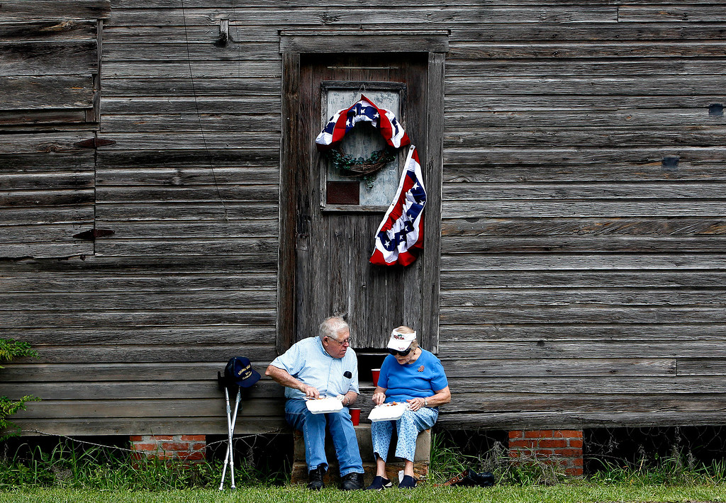 Description of . Robert and Gena Phillips eat fried fish, coleslaw and hushpuppies following the annual Independence Day parade on Thursday, July 4, 2013 in Micanopy, Fla. (AP Photo/The Gainesville Sun, Matt Stamey)