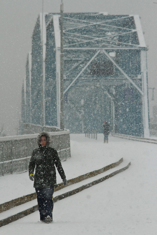 Description of . Ashley Cuticchia walks across the Walnut Street Bridge as snow accumulates on Wednesday, Feb. 12, 2014 in Chattanooga, Tenn. The bridge is a pedestrian bridge that spans the Tennessee River. Slushy highways and streets were mostly desolate and ice encased trees and sent them crashing into power lines, knocking out electricity to a wide swath of the South as the winter-weary region was hit with its second winter storm in two weeks. (AP Photo/Chattanooga Times Free Press, Dan Henry)