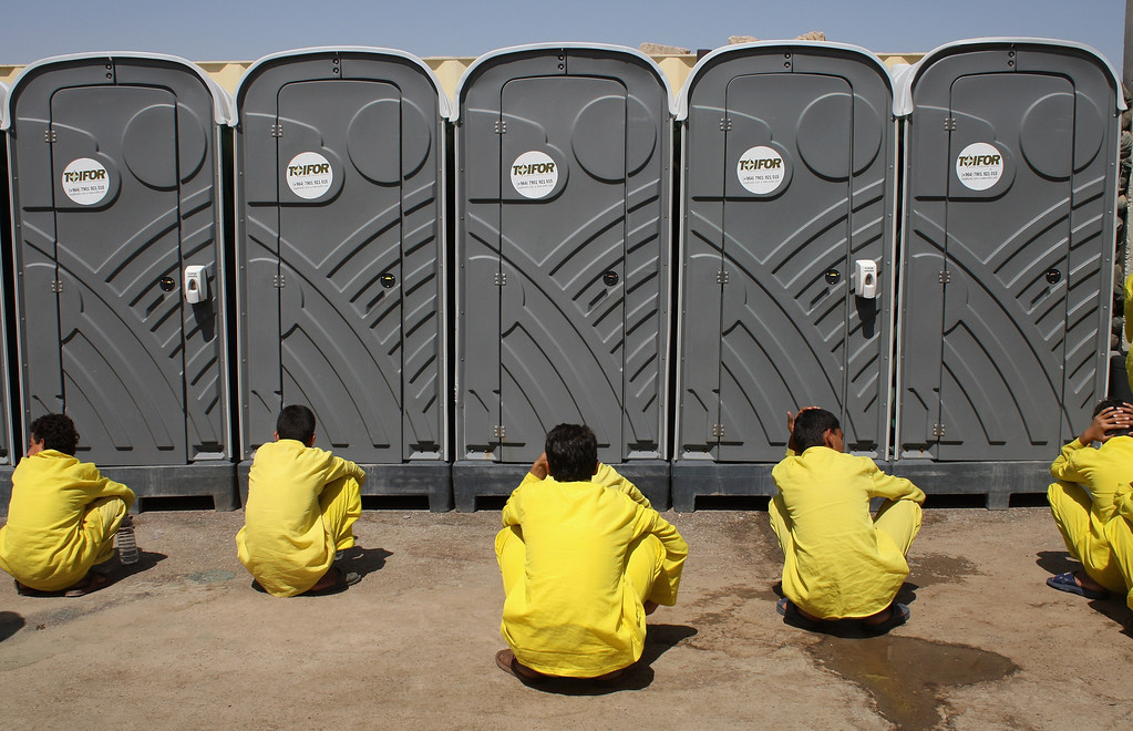 "Description of . Juvenile detainees wait for their turn outside portable bathrooms at the ""House of Wisdom\"" school operated by the U.S. military near the Camp Cropper detention center September 19, 2007 in Baghdad Iraq. More than 800 juvenile detainees were in American custody at the center. Most were captured during this year\'s American troop \""surge\"" in Baghdad. They attend six classes -  Arabic, Science, Math, History, Civics and English every three days. Many of the detainees, ages 12-17 years old, were captured while planting roadside bombs or IEDs targeting U.S. forces, according to military officials.  (Photo by John Moore/Getty Images)"