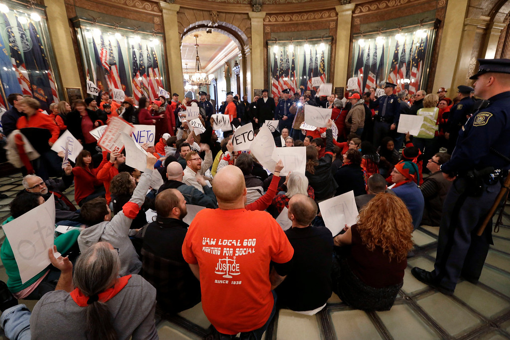 . Protesters sit in the rotunda of the State Capitol in Lansing, Mich., Tuesday, Dec. 11, 2012. The crowd is protesting right-to-work legislation passed last week. Michigan could become the 24th state with a right-to-work law next week. Rules required a five-day wait before the House and Senate vote on each other\'s bills; lawmakers are scheduled to reconvene Tuesday and Gov. Snyder has pledged to sign the bills into law. (AP Photo/Paul Sancya)