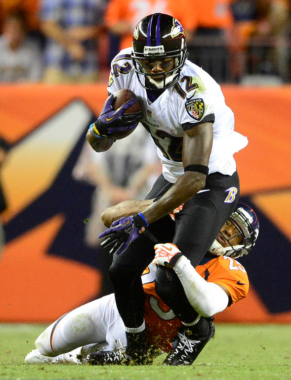 Description of . Denver Broncos cornerback Chris Harris (25) tackles Baltimore Ravens wide receiver Jacoby Jones (12).  (Photo by AAron Ontiveroz/The Denver Post)