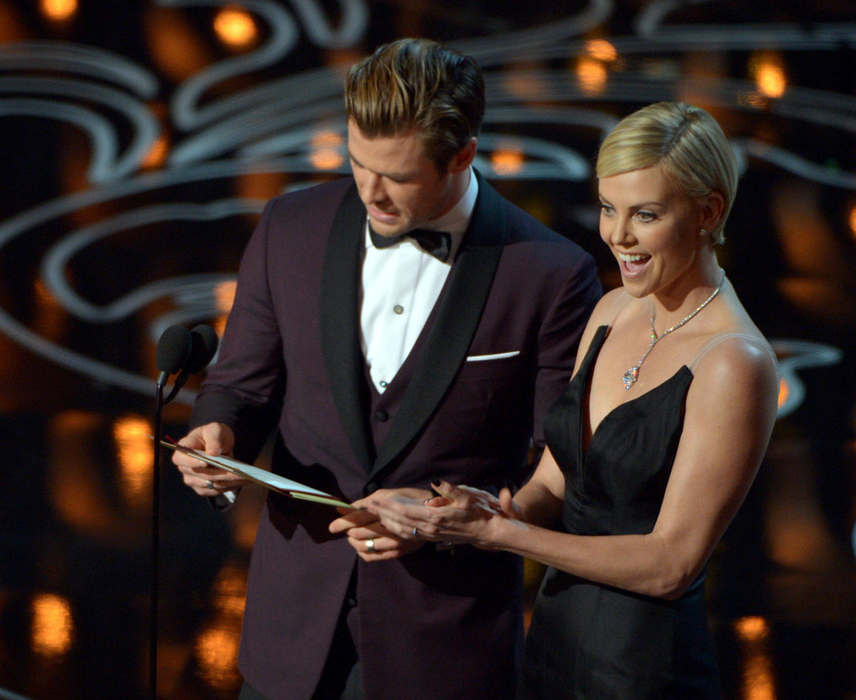 Description of . Chris Hemsworth, left, and Charlize Theron present an award during the Oscars at the Dolby Theatre on Sunday, March 2, 2014, in Los Angeles.  (Photo by John Shearer/Invision/AP)