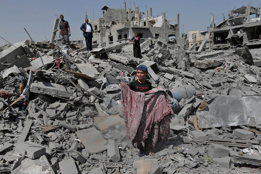 Description of . Palestinians salvage belongings from the rubble of their destroyed house in the heavily bombed town of Beit Hanoun, Gaza Strip, close to the Israeli border, Friday, Aug. 1, 2014. A three-day Gaza cease-fire that began Friday quickly unraveled, with Israel and Hamas accusing each other of violating the truce. (AP Photo/Lefteris Pitarakis)