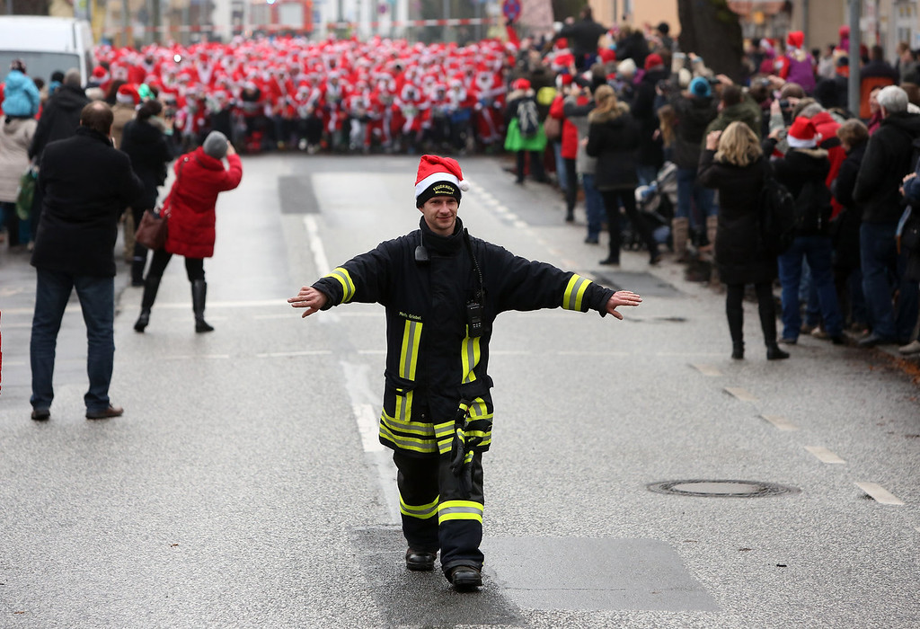 Description of . A fireman clears the road for the 5th annual Michendorf Santa Run (Michendorfer Nikolauslauf) on December 8, 2013 in Michendorf, Germany. Over 900 people took part in this year's races, which included one for children and one for adults.  (Photo by Adam Berry/Getty Images)