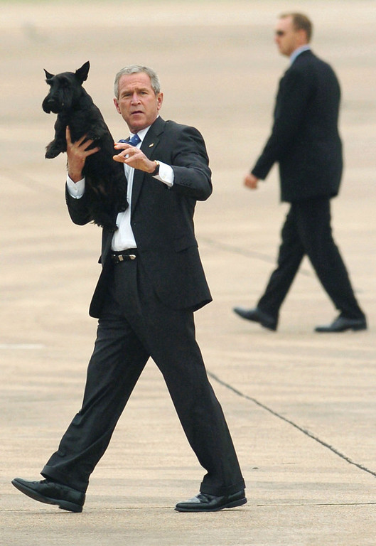 Description of . President Bush, holding his dog Barney, waves as he walks toward Marine One after arriving at TSTC Airfield, Tuesday, Aug. 2, 2005, in Waco, Texas.  Bush is headed for his Crawford, Texas ranch. (AP Photo/Duane A. Laverty)