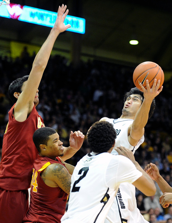 Description of . University of Colorado's Sabatino Chen takes a shot over Eric Wise, center, and Omar Oraby during a game against the University of Southern California on Thursday, Jan. 10, at the Coors Event Center on the CU campus in Boulder. Jeremy Papasso/Daily Camera