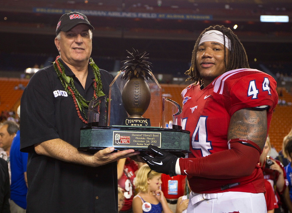 Description of . SMU coach June Jones and linebacker Taylor Reed (44) hold the Hawaii Bowl trophy after SMU defeated Fresno State 43-10 in the college football game Monday, Dec. 24, 2012, in Honolulu. (AP Photo/Eugene Tanner)