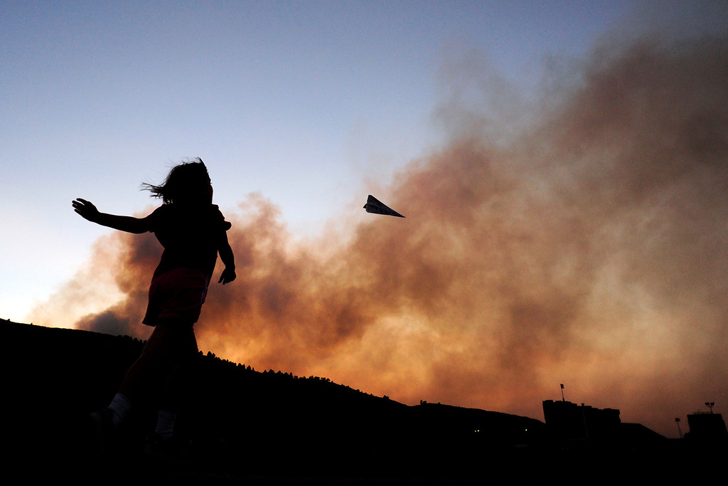 Description of . Charlotte Frank, 8, throws a paper airplane while on a walk with her father near Hughes Stadium as the High Park Fire burns west of Fort Collins on Sunday, June 17, 2012. AAron Ontiveroz, The Denver Post