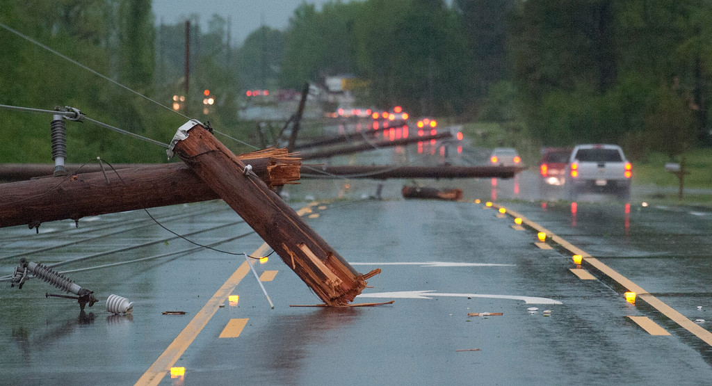 Description of . Downed utility poles lie across a road in the Clements community west of Athens, Ala., after a tornado on Monday, April 28, 2014. Local officials reported six deaths in Alabama from the tornado. State emergency officials could not immediately confirm those deaths. Thousands of customers were without power in Alabama and Kentucky, where severe storms caused widespread damages. (AP Photo/The Decatur Daily, Brennen Smith)