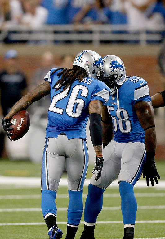 Description of . DETROIT, MI - SEPTEMBER 29:  Louis Delmas #26 of the Detroit Lions celebrates his first-quarter interception with teammate Ashlee Palmer #58 of the Detroit Lions at Ford Field on September 29, 2013 in Detroit, Michigan. (Photo by Gregory Shamus/Getty Images)