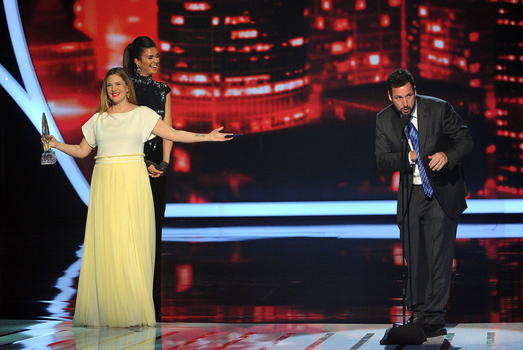 Description of . LOS ANGELES, CA - JANUARY 08:  Actor Adam Sandler (R) accepts the Favorite Comedic Movie Actor award from actress Drew Barrymore onstage at The 40th Annual People's Choice Awards at Nokia Theatre L.A. Live on January 8, 2014 in Los Angeles, California.  (Photo by Kevin Winter/Getty Images)