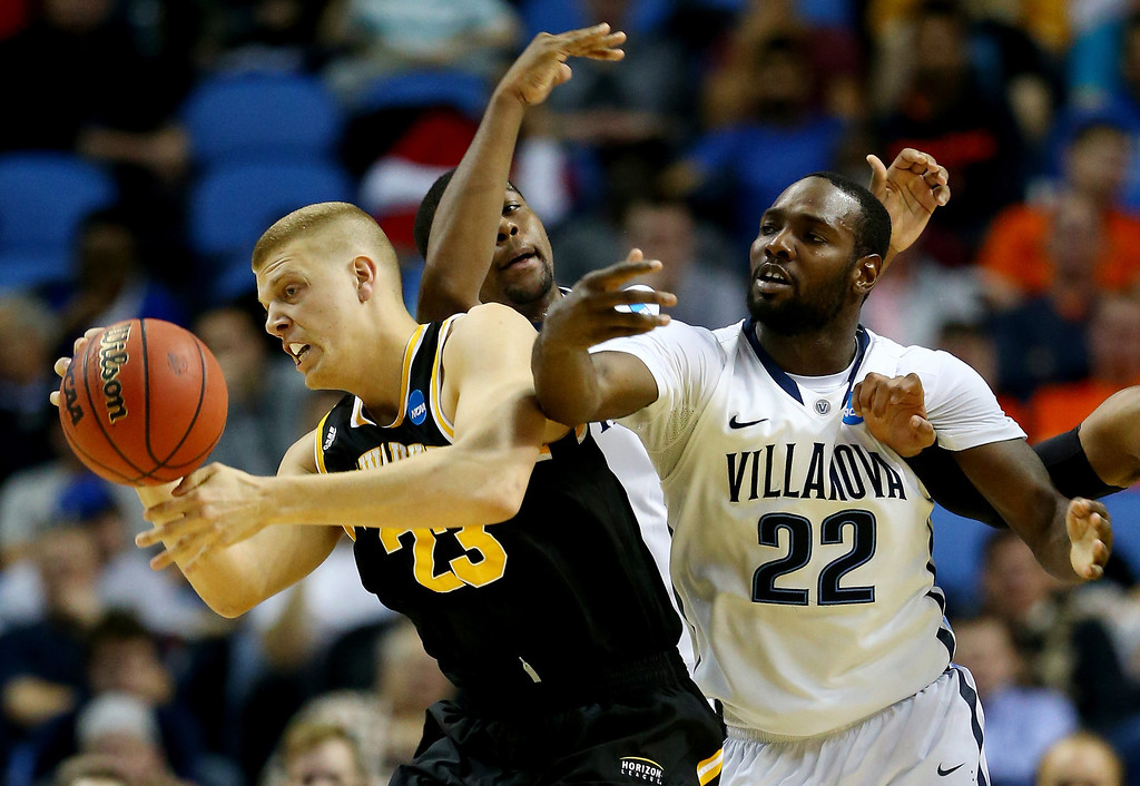 Description of . BUFFALO, NY - MARCH 20:  J.J. Panoske #23 of the Milwaukee Panthers and JayVaughn Pinkston #22 of the Villanova Wildcats go for a lose ball during the second round of the 2014 NCAA Men's Basketball Tournament at the First Niagara Center on March 20, 2014 in Buffalo, New York.  (Photo by Elsa/Getty Images)