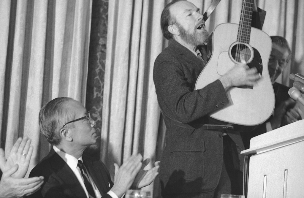 Description of . Retiring U.N. Secretary General U. Thant, left, is shown listening to a song by folk singer Pete Seeger at luncheon honoring Thant at the hotel Pierre in New York on Dec. 14, 1971. (AP Photo/Marty Lederhandler)