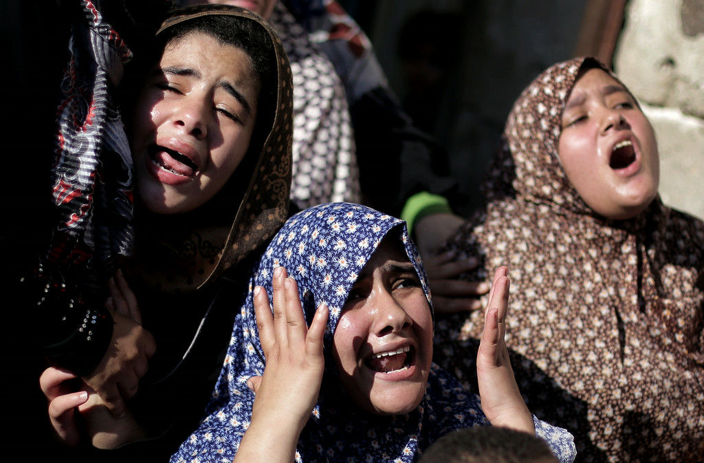 Description of . Palestinian relatives of four boys from the same extended Bakr family, grieve during their funeral in Gaza City, Wednesday, July 16, 2014.  The four boys, who were cousins and ages 9 to 11, were killed while playing on a beach off a coastal road west of Gaza City, said Ashraf Al Kedra, a Palestinian doctor. Seven others _ adults and children _ were wounded in the strike, he said. (AP Photo/Khalil Hamra)