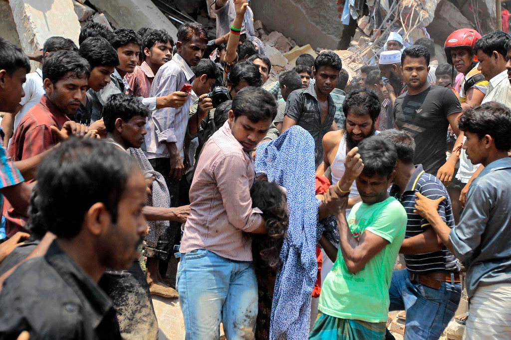 Description of . Rescue workers carry a victim's body after an eight-story building housing several garment factories collapsed in Savar, near Dhaka, Bangladesh, Wednesday, April 24, 2013. (AP Photo/ A.M. Ahad)