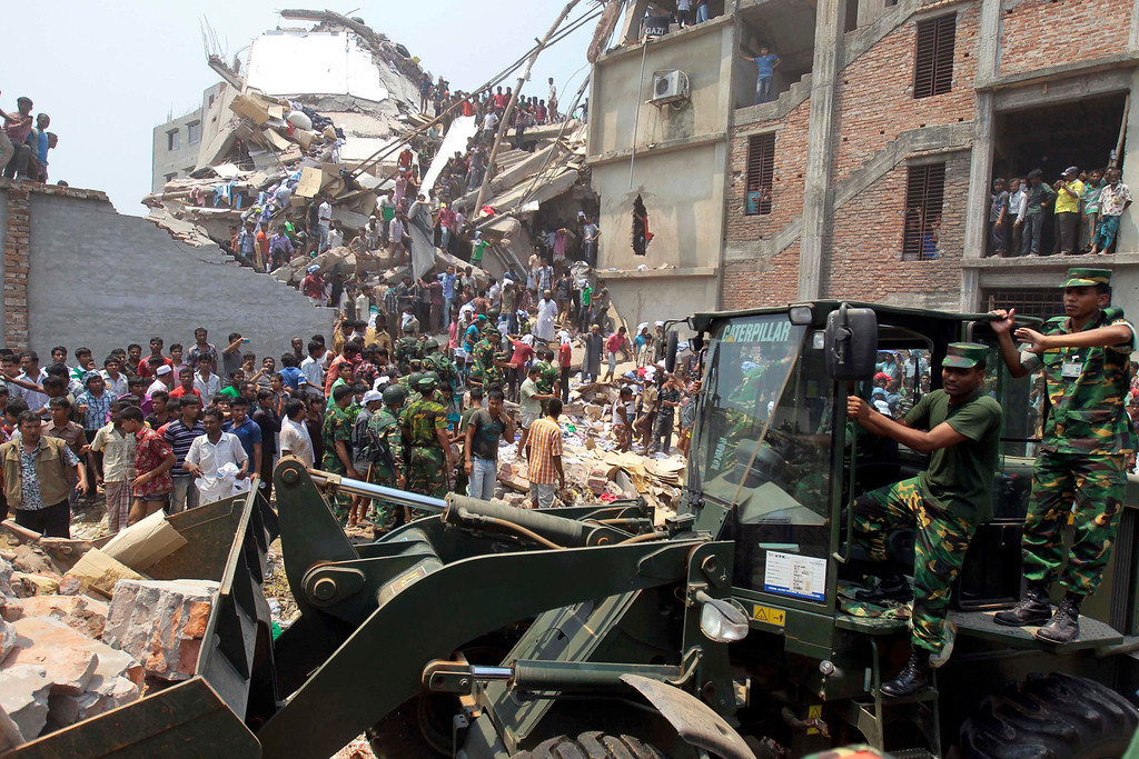 Description of . Bangladeshi soldiers use an earthmover for rescue operations after an eight-story building housing several garment factories collapsed in Savar, near Dhaka, Bangladesh, Wednesday, April 24, 2013.  (AP Photo/ A.M. Ahad)