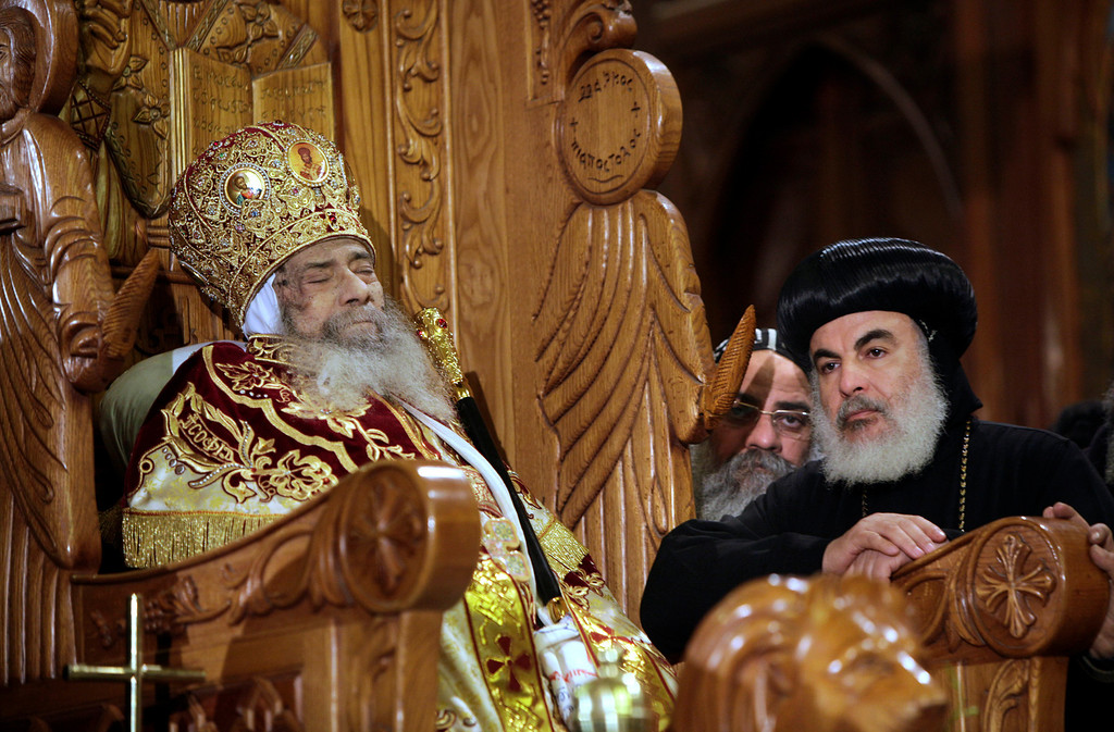 Description of . In this March 18, 2012 file photo, Archbishops stand next to the body of Pope Shenouda III is seated on the throne of Mar Morqos, or St. Mark, as mourners gather for the viewing of the patriarch at the Coptic Orthodox Church in Cairo, Egypt. Pope Shenouda III, the patriarch of the Coptic Orthodox Church who led Egypt's Christian minority for 40 years during a time of increasing tensions with Muslims, died. He was 88. (AP Photo/Amr Nabil, File)