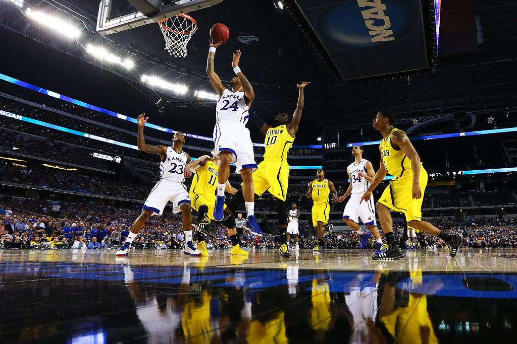 Description of . ARLINGTON, TX - MARCH 29:  Travis Releford #24 of the Kansas Jayhawks shoots against the Michigan Wolverines in the first half during the South Regional Semifinal round of the 2013 NCAA Men\'s Basketball Tournament at Dallas Cowboys Stadium on March 29, 2013 in Arlington, Texas.  (Photo by Tom Pennington/Getty Images)