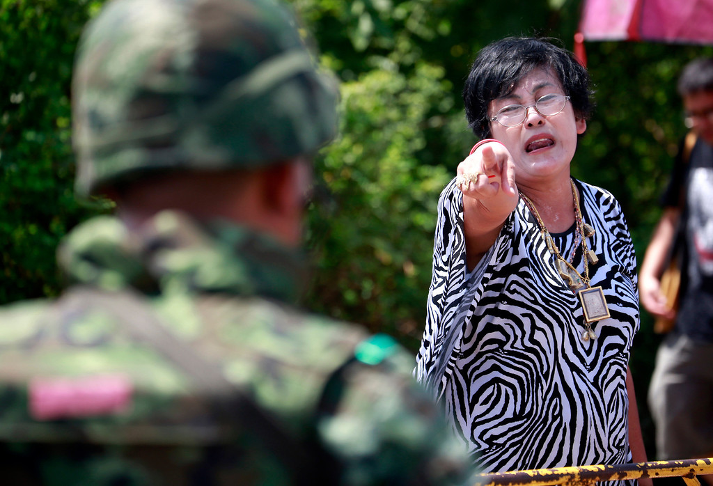 Description of . A pro-government protester points at a soldier during a cleanup at a pro-government demonstration site on the outskirts of Bangkok, Thailand Friday, May 23, 2014. T(AP Photo/Wason Wanichakorn)